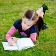 Stock Photo: Little girl reading on grass - from above
