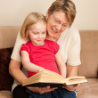 A grandmother or Nanny reading to a 4 year old little girl — Stock Photo