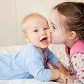 A big sister kisses her little brother — Stock Photo