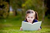 Een klein meisje genieten van lezing buiten op het gras — Stockfoto