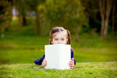 A little girl comtemplating her reading outside. — Stock Photo