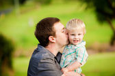 A little boy plays with his Dad in an outdoor field — Stock Photo