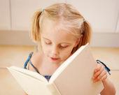 En liten fyra-åriga flicka som läser — Stockfoto