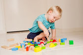 A cute little boy plays with blocks — Stock Photo