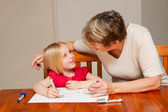 A little girl drawing with her carer — Stock Photo