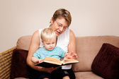 A grandmother reads to a little boy — Stock Photo
