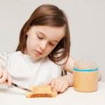 en ung flicka gör en jordnötssmör smörgås — Stockfoto