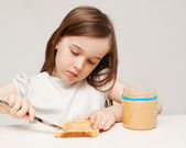 A young girl makes a peanut butter sandwich — Stock Photo