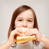A young girl eats a sandwhich made of wholemeal bread — Stock Photo