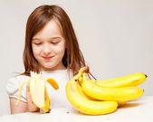 A young girl eats a banana — Stock Photo
