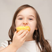 A young girl eats a donut — Stock Photo