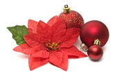 Fake poinsettia with christmas balls — Stock Photo