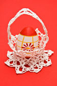 Easter egg in white crochet basket — Stock Photo