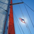 Sails and American flag against blue sky — Stock Photo #8892118