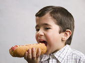Boy eating hotdog — Stock Photo