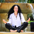 Beautiful businesswoman practicing yoga outdoors — Stock Photo