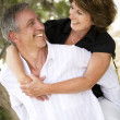 Mature couple smiling and embracing. - Stock Photo