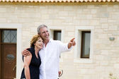 Mature couple in front of their house — Stock Photo