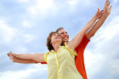 Mature couple with arms outstretched — Stock Photo