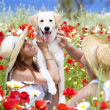 Happy young couple playing with dog on a meadow — Stock Photo #8979430