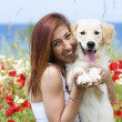 Happy young woman playing with her dog on a meadow — Stock Photo