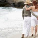 Young romantic couple walking along the beach — Stock Photo