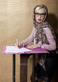 Blonde woman in a scarf and goggles writing pen on paper — Stock Photo