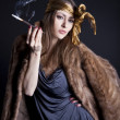 Girl in a fur coat with a cigarette studio portrait — Stock Photo