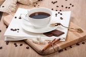Black coffee with sugar chocolate and cinnamon — Stock Photo