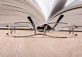 Open book with glasses — Stock Photo