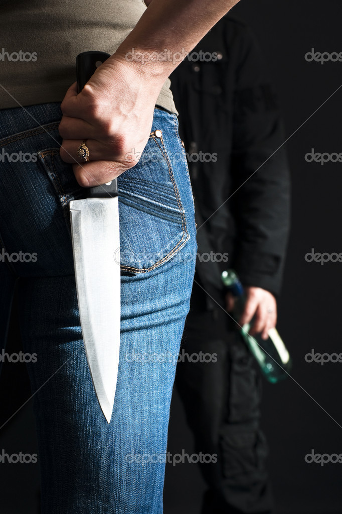 Young woman with a knife facing her drunk husband. — Stock Photo #8724983