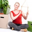 Young woman with house symbol sits between move cardboards and plant — Foto de Stock