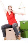 ボックスを移動するのに座っている家のシンボルを持つ若い女 — ストック写真