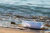 Mensaje en una botella en la oleada — Foto de Stock