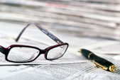 Reading glasses and ballpoint pen — Stockfoto