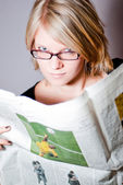 Young woman with glasses reading newspaper V1 — Stock Photo