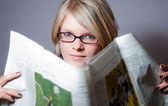 Mulher jovem com óculos lendo jornal v2 — Fotografia Stock