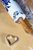 Dough and rolling pin with heart ramekins — Stock Photo
