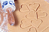 Rolling pin with many gouged heart ramekins — Stock Photo