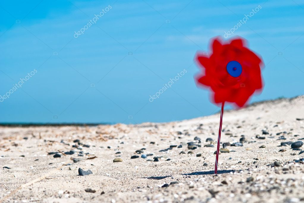 A red wind turbine on the sandy beach with sea in the background — Stock Photo #8812749