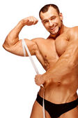 Muscular and tanned male body parts is being measured — Stock Photo