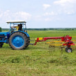 Stock Photo: A tractor turning cut hay in a field.