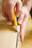 Men unpacking box with cutter — Stock Photo