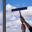 Hands with squeegee cleaning the misted window — Stock Photo