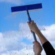 Hand with squeegee cleaning the misted window — Stock Photo