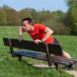 Mexercising doing pressups on Park Bench in Sun — Stock Photo #8737243