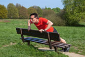 Man exercising doing pressups on a Park Bench in the Sun — Stock Photo