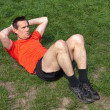 Stock Photo: Mexercising doing Situps on Grass in sunshine