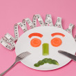Sad Diet Salad Face on White Plate Pink Background — Stock Photo