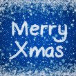 Christmas Blue Background with Merry Xmas Text in Snow Writing — Stock Photo #8859410